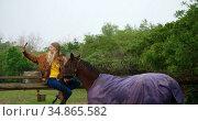 Woman taking selfie with horse on wooden fence 4k. Стоковое видео, агентство Wavebreak Media / Фотобанк Лори