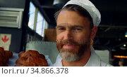 Smiling chef holding ray of baked buns 4k. Стоковое видео, агентство Wavebreak Media / Фотобанк Лори