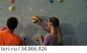 Coach training a woman to climb artificial wall 4k. Стоковое видео, агентство Wavebreak Media / Фотобанк Лори