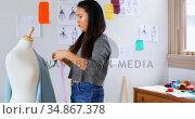 Fashion designer looking at sketch and measuring the fabric 4k. Стоковое видео, агентство Wavebreak Media / Фотобанк Лори