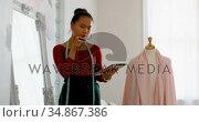 Fashion designer talking on the phone while working on dress makers model 4k. Стоковое видео, агентство Wavebreak Media / Фотобанк Лори