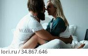 Couple kissing on bed in bedroom 4k. Стоковое видео, агентство Wavebreak Media / Фотобанк Лори