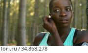 Female jogger putting headphone in her ear 4k. Стоковое видео, агентство Wavebreak Media / Фотобанк Лори