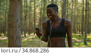 Female jogger using mobile phone in the forest 4k. Стоковое видео, агентство Wavebreak Media / Фотобанк Лори