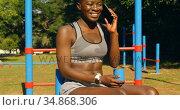 Female athlete talking on mobile phone in the park 4k. Стоковое видео, агентство Wavebreak Media / Фотобанк Лори