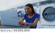 Woman using laptop at laundromat 4k. Стоковое видео, агентство Wavebreak Media / Фотобанк Лори