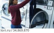 Woman removing clothes from washing machine 4k. Стоковое видео, агентство Wavebreak Media / Фотобанк Лори