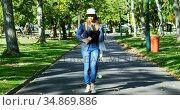 Woman with skateboard walking on street near park 4k. Стоковое видео, агентство Wavebreak Media / Фотобанк Лори