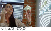 Female executive removing sticky note while talking on mobile phone 4k. Стоковое видео, агентство Wavebreak Media / Фотобанк Лори