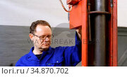 Mechanic using hydraulic lift in garage 4k. Стоковое видео, агентство Wavebreak Media / Фотобанк Лори