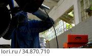 Mechanic using wielding torch on a car in garage 4k. Стоковое видео, агентство Wavebreak Media / Фотобанк Лори