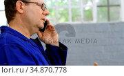 Mechanic talking on mobile phone in garage 4k. Стоковое видео, агентство Wavebreak Media / Фотобанк Лори