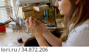 Female jewelry designer examining ring in workshop 4k. Стоковое видео, агентство Wavebreak Media / Фотобанк Лори