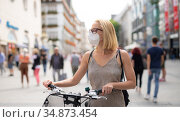 Woman walking by her bicycle on pedestrian city street wearing medical face mask in public to prevent spreading of corona virus. New normal during covid epidemic. Стоковое фото, фотограф Matej Kastelic / Фотобанк Лори
