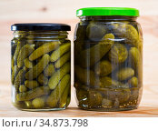 Pickled cucumbers with spices in glass jar on a wooden surface. Стоковое фото, фотограф Яков Филимонов / Фотобанк Лори