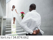 Man standing at bottom of steps offering roses to girlfriend hiding engagement ring. Стоковое фото, агентство Wavebreak Media / Фотобанк Лори