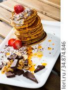 Stack of sweet pancakes with fruit, honey, chocolate and whipped cream. Стоковое фото, фотограф Яков Филимонов / Фотобанк Лори