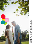 Hip young couple holding colourful balloons in the park. Стоковое фото, агентство Wavebreak Media / Фотобанк Лори