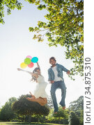Hip young couple holding colourful balloons in the park and jumping. Стоковое фото, агентство Wavebreak Media / Фотобанк Лори