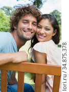 Happy young couple sitting on park bench together. Стоковое фото, агентство Wavebreak Media / Фотобанк Лори
