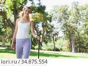 Fit woman walking with a hiking pole through the countryside. Стоковое фото, агентство Wavebreak Media / Фотобанк Лори