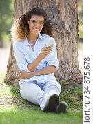 Pretty woman sitting by a tree texting and smiling at camera. Стоковое фото, агентство Wavebreak Media / Фотобанк Лори