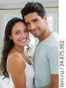 Attractive couple standing in an embrace smile at camera. Стоковое фото, агентство Wavebreak Media / Фотобанк Лори