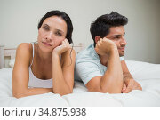 Unhappy couple on bed distant and having troubles. Стоковое фото, агентство Wavebreak Media / Фотобанк Лори