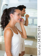 Attractive couple use toothbrush to clean their teeth. Стоковое фото, агентство Wavebreak Media / Фотобанк Лори