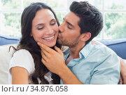 Boyfriend kisses girlfriend on cheek on the couch. Стоковое фото, агентство Wavebreak Media / Фотобанк Лори
