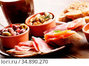 Tapas of salmon, mussels, jamon and olives on ceramic plate with glass... Стоковое фото, фотограф Olena Mykhaylova / easy Fotostock / Фотобанк Лори