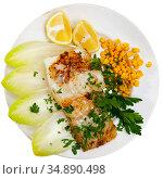 Pink cusk-eel fillet with endive, pickled corn, lemon and greens. Стоковое фото, фотограф Яков Филимонов / Фотобанк Лори