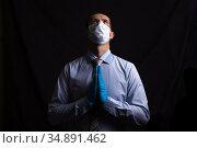 business man masked doctor prays, on a dark background. Стоковое фото, фотограф Владимир Арсентьев / Фотобанк Лори