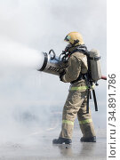 One firefighter extinguish fire from fire hose, using firefighting water-foam barrel with air-mechanical foam (2019 год). Редакционное фото, фотограф А. А. Пирагис / Фотобанк Лори
