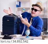 Young employee preparing for vacation trip. Стоковое фото, фотограф Elnur / Фотобанк Лори