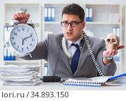 Businessman smoking holding human skull and an alarm clock in th. Стоковое фото, фотограф Elnur / Фотобанк Лори