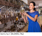 adult female choosing natural dried herbs sold by weight in eco shop. Стоковое фото, фотограф Яков Филимонов / Фотобанк Лори