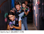 Portrait of happy young friends playing laser tag game with laser guns in dark corridor. Стоковое фото, фотограф Яков Филимонов / Фотобанк Лори