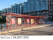 Red design tram stop by Stefan Lindfors in in center of city. It is located on Fredrikinkatu in the Kamppi district. Helsinki, Finland. Редакционное фото, фотограф Кекяляйнен Андрей / Фотобанк Лори