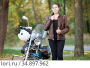 Stylish girl in a brown leather jacket with a classic motorcycle standing in autumn park. Стоковое фото, фотограф Кекяляйнен Андрей / Фотобанк Лори