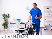 Young male doctor and skeleton in wheel-chair. Стоковое фото, фотограф Elnur / Фотобанк Лори