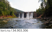 Water dam in the forest - water falls down under the bridge in shallow water. Стоковое видео, видеограф Константин Шишкин / Фотобанк Лори