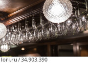 Wineglasses and goblets hang above the ba. Стоковое фото, фотограф Юрий Бизгаймер / Фотобанк Лори