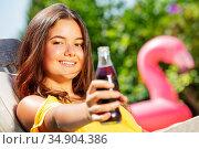 Teenage long hair girl give soda glass bottle. Стоковое фото, фотограф Сергей Новиков / Фотобанк Лори