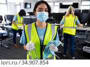 Portrait of woman wearing hi vis vest and face mask holding cleaning cloth and disinfectant. Стоковое фото, агентство Wavebreak Media / Фотобанк Лори