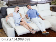 Loving couple are choosing of sofa with a rising bottom. Стоковое фото, фотограф Яков Филимонов / Фотобанк Лори