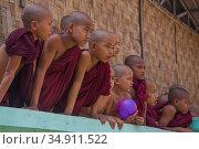 Мальчики-послушники буддистского монастыря выглядывают из-за забора. Янгон, Мьянма (2016 год). Редакционное фото, фотограф Виктор Карасев / Фотобанк Лори