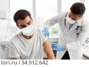 patient and doctor in masks doing vaccination. Стоковое фото, фотограф Syda Productions / Фотобанк Лори