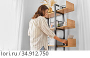 woman arranging books on shelving at home. Стоковое фото, фотограф Syda Productions / Фотобанк Лори