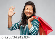 happy asian woman with shopping bags waving hand. Стоковое фото, фотограф Syda Productions / Фотобанк Лори